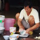 Vietnam...sidewalk eatery , washing dishes.